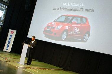 Baki a prezentációban - Takeuchi Hisashi mögött egy előző generációs Swift-et mutatnak a jubileumi matricázással