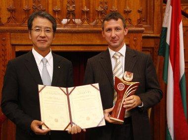 A Magyar Termék Nagydíjat a Magyar Suzuki Zrt. nevében Hisashi Takeuchi vezérigazgató és Kocsis József minőségbiztosítási igazgató vette át a Parlament felsőházi termében.