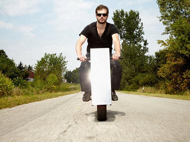 Nem számítógépház, hanem egy elektromos motorkerékpár van a képen látható úr lába között