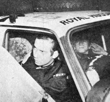 """A fehér Austin tetején a """"Royal Hussars"""" felírás, az ajtókivágásban pedig a """"Királyi Huszárezred"""" kiszolgált kapitánya, Michail, a kenti herceg látható, mint a Maxi másodpilótája"""