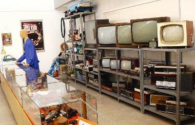 """A polcokon követhető a tévék, rádiók és porszívók fejlődéstörténete, a pultban """"apró holmi"""", legfelül pedig minden akkori kissrác álma (az enyém is), a pedálos Moszkvics"""