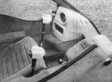 A kabin belülről. A kormány a versenybiciklikére emlékeztet. A kárpitozott burkolat alatt van a motor és az akkumulátor, a sebességváltókar lóg ki belőle. Az összes szükséges kapcsoló a kormányon van