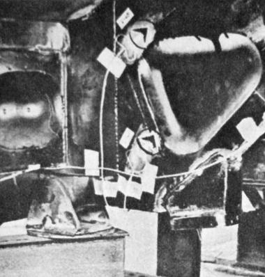 Az 556-os kísérleti modell vázszerkezetén a vizsgálatok során ilyen mérőbélyegeket helyeztek el. Az elektromos nyúlásmérő bélyegek a feszültség irányát – a képen nyilakkal jelölve – mutatják