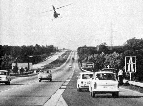 Helikopter és repülőgép ellenőrzi az egész útvonalat. Ez a kép kora délután készült, a forgalom még csak most kezdődött. Fehéren csillog a napfényben a párhuzamos úttest, amely nem is oly sokára Martonvásárig már valódi autópályává változtatja az M7-est